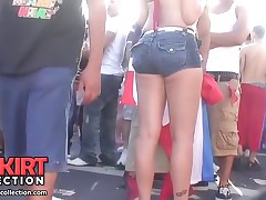 Sexy babe in bikini bra and short jeans shorts is seductively shaking the ass in crowd
