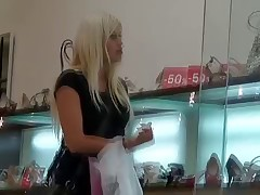 Seducing blonde in black butt pants is followed by the guy with camera while shopping