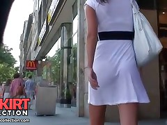 The hot girl is a light summer dress is walking and her booty is sexily moving upskirt