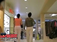 Two girlfriends are in the trading center teasing males with the tight butt jeans view